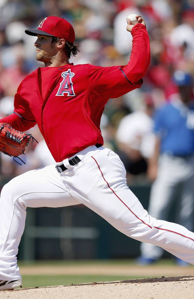 Los Angeles Angels' C.J. Wilson throws a pitch against the Kansas City Royals during the first inning of a spring training baseball game Friday, March 21, 2014, in Tempe, Ariz