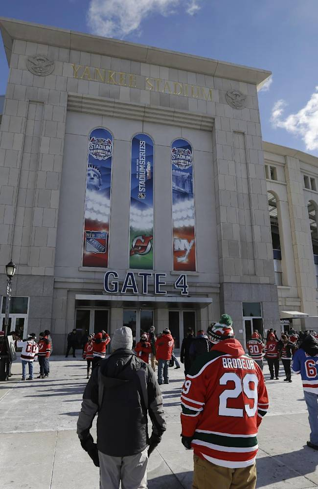 Fans arrive before an outdoor NHL hockey game between the New Jersey Devils and the New York Rangers Sunday, Jan. 26, 2014, at Yankee Stadium in New York