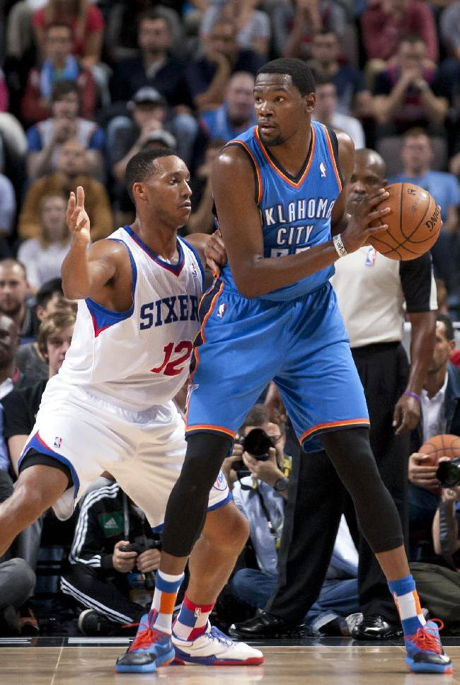 Oklahoma City Thunder's Kevin Durnat, right, keeps the ball from Philadelphia 76ers' Evan Turner during their NBA preseason basketball game at the Phones4 u Arena in Manchester, England, Tuesday, Oct. 8, 2013