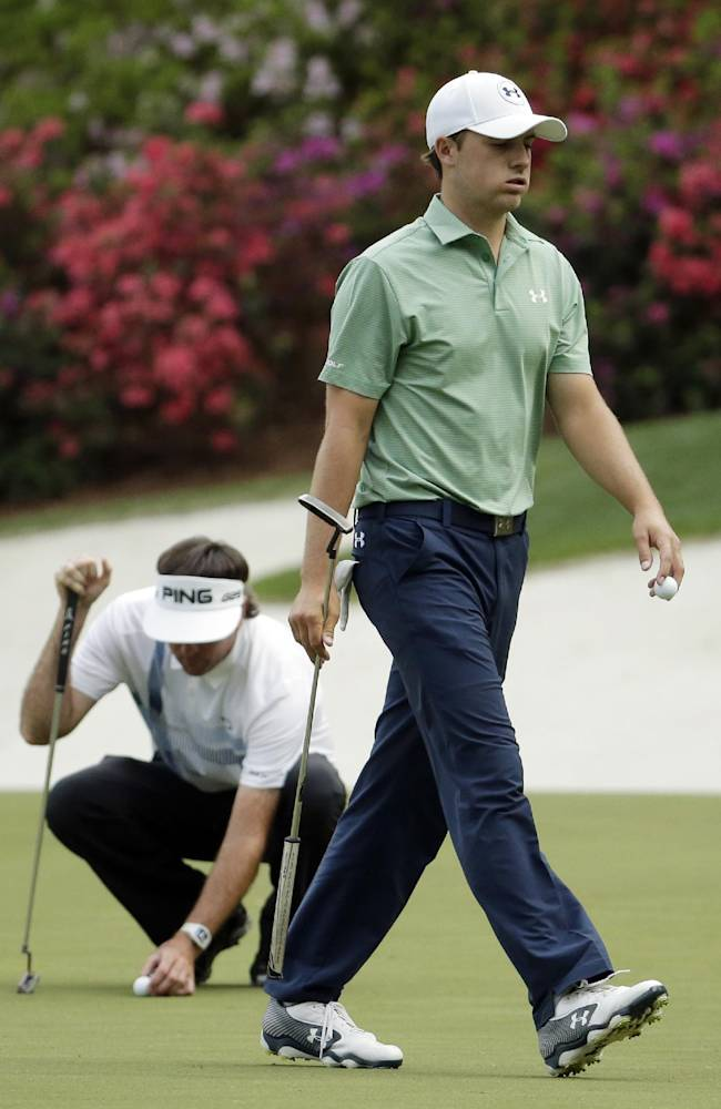 Bubba Watson, left, lines up his putt as Jordan Spieth walks off the 13th green during the fourth round of the Masters golf tournament Sunday, April 13, 2014, in Augusta, Ga
