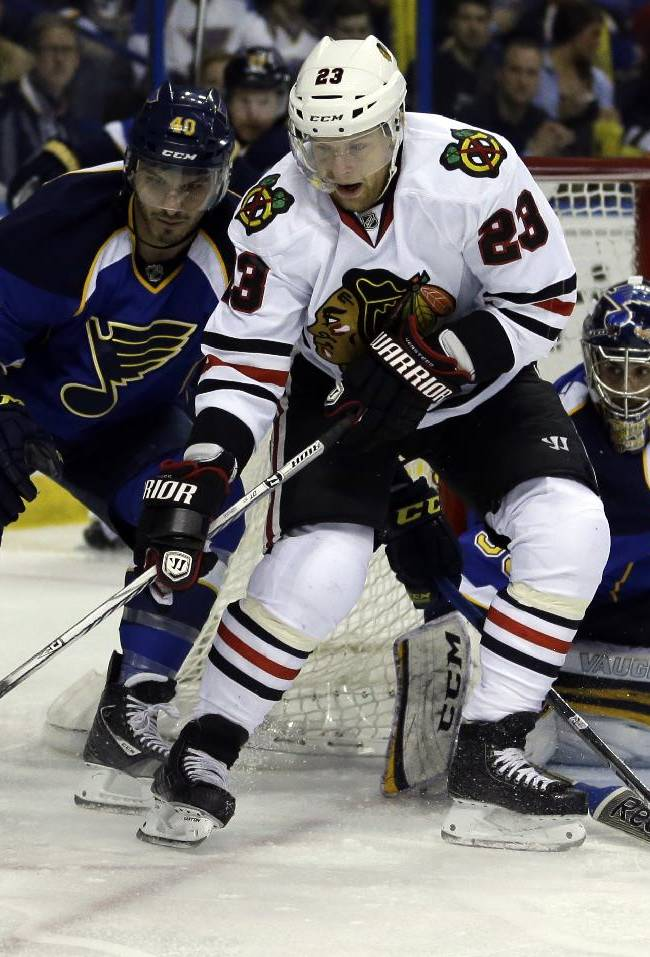 Chicago Blackhawks' Kris Versteeg,center, handles the puck as St. Louis Blues goalie Ryan Miller, right, and Maxim Lapierre, left, defend during the first period in Game 5 of a first-round NHL hockey playoff series Friday, April 25, 2014, in St. Louis