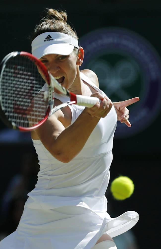 Simona Halep of Romania hits a return to Eugenie Bouchard of Canada during their women's singles semifinal match at the All England Lawn Tennis Championships in Wimbledon, London, Thursday, July 3, 2014