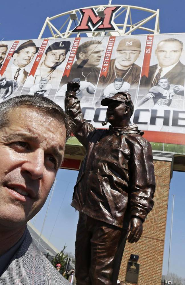 Baltimore Ravens coach John Harbaugh is interviewed next to a statue of him that was unveiled, Saturday, April 19, 2014, at Miami (Ohio) University in Oxford, Ohio, where Harbaugh was inducted into the school's Cradle of Coaches