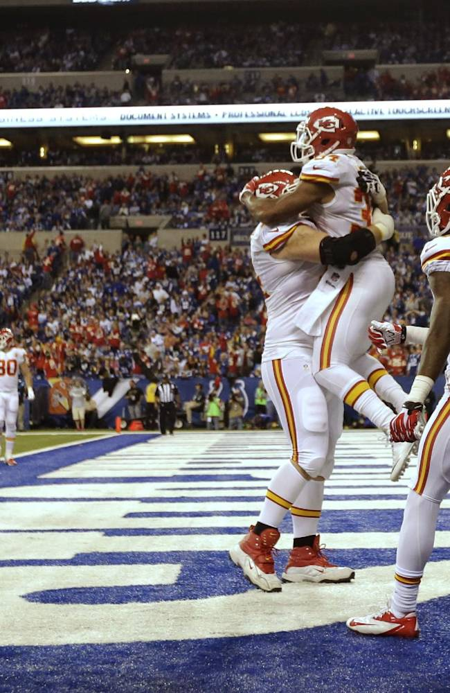 After scoring a 10-yard touchdown reception, Kansas City Chiefs running back Knile Davis (34) jumps into the arms of Geoff Schwartz (74) as wide receiver A.J. Jenkins (15) moves in during the second half of an NFL wild-card playoff football game Saturday, Jan. 4, 2014, in Indianapolis. Colts defensive back Josh Gordy (27) walks away