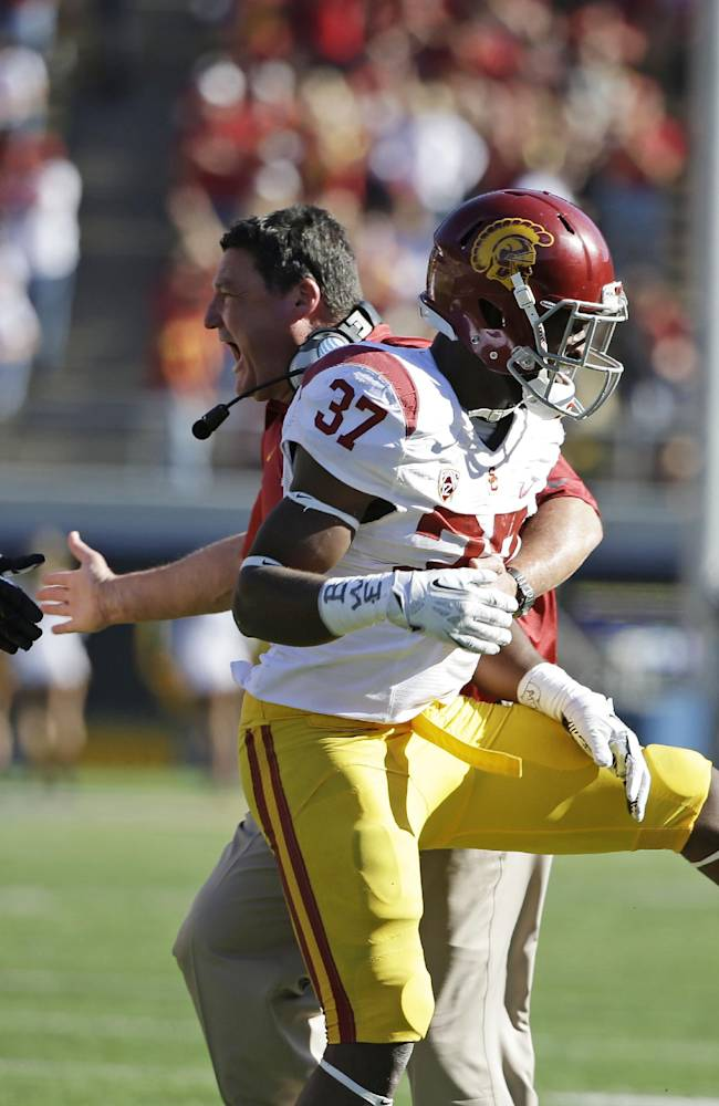 Southern California coach Ed Orgeron greets tailback Javorius Allen (37) and tackle Kevin Graf, left, after Allen scored a touchdown on a pass reception during the second quarter of an NCAA college football game against California on Saturday, Nov. 9, 2013, in Berkeley, Calif