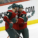 Minnesota Wild center Mikko Koivu (9), of Finland, and left wing Zach Parise (11) celebrate Parise's empty-net goal against the San Jose Sharks during the third period of an NHL hockey game in St. Paul, Minn., Sunday, Dec. 8, 2013. The Wild won 3-1 The As
