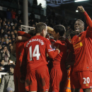 Liverpool's players celebrate Steven Gerrard's penalty goal against Fulham during their English Premier League soccer match at Craven Cottage, London, Wednesday, Feb. 12, 2014