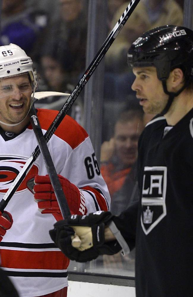 Los Angeles Kings defenseman Willie Mitchell, right, rests his stick against the neck of Carolina Hurricanes defenseman Ron Hainsey during a stoppage in play in the third period of an NHL hockey game, Saturday, March 1, 2014, in Los Angeles. The Kings won 3-1