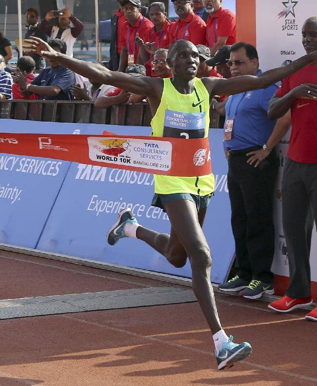 U.S. Olympian Carl Lewis, right, watches Kenyan athlete Geoffrey Kamworor cross the finish line to win the TCS World 10K Bangalore 2014 run for men in Bangalore, India, Sunday, May 18, 2014. According to organizers, the event had eight races with total prize money of USD 170,000