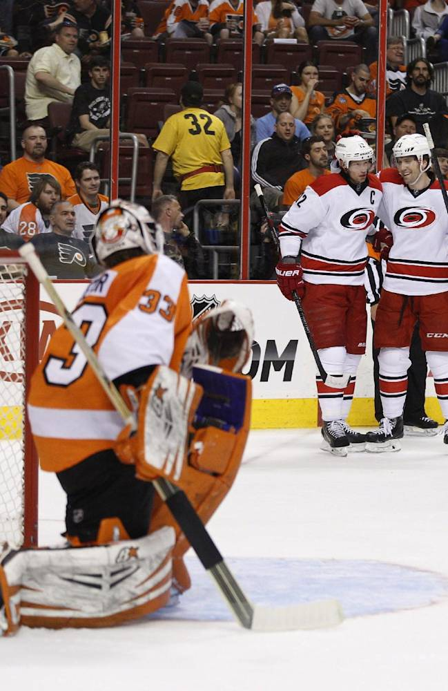 Carolina Hurricanes' Eric Staal, left rear, celebrates with Brett Bellemore after Staal scored against Philadelphia Flyers goalie Cal Heeter during the first period of an NHL hockey game, Sunday, April 13, 2014, in Philadelphia