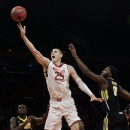 Maryland's Alex Len (25) drives past Iowa's Anthony Clemmons (5) and Gabriel Olaseni, right, during the first half of an NIT semifinal basketball game Tuesday, April 2, 2013, in New York. (AP Photo/Frank Franklin)
