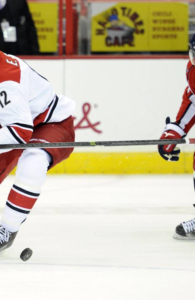Washington Capitals right wing Joel Ward (42) battles for the puck against Carolina Hurricanes center Eric Staal (12) during the first period an NHL hockey game, Thursday, Oct. 10, 2013, in Washington