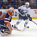 Vancouver Canucks' Alexandre Burrows (14) is stopped by Edmonton Oilers goalie Ben Scrivens (30) during first period NHL hockey action in Edmonton, Alta., on Saturday April 12, 2014 The Associated Press