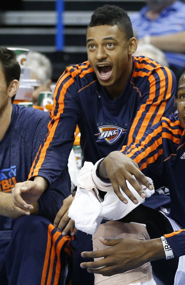 Oklahoma City Thunder's Nick Collison, left, Diante Garrett, center, and Kevin Durant, right, cheer from the bench during the first quarter of a preseason NBA basketball game against the Denver Nuggets in Oklahoma City, Tuesday, Oct. 15, 2013