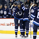 Winnipeg Jets Dustin Byfuglien (33) celebrates with Tobias Enstrom (39) after he opened the scoring against the Minnesota Wild's during second period pre-season NHL hockey action in Winnipeg, Monday, Sept. 22, 2014 The Associated Press