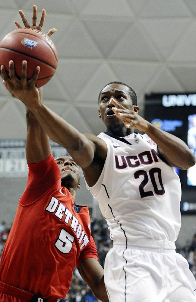 Connecticut's Lasan Kromah, right, drives to the basket as Detroit's Matthew Grant defends during the second half of an NCAA college basketball game Thursday, Nov. 14, 2013, in Storrs, Conn. Connecticut won 101-55