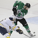 Dallas Stars defenseman Sergei Gonchar (55) and Buffalo Sabres left wing Ville Leino (23) battle for control of the puck during the first period of an NHL hockey game Monday, March 3, 2014, in Dallas The Associated Press