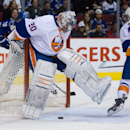 New York Islanders' goalie Evgeni Nabokov, left, of Russia, tries to kick the puck away after losing sight of it as teammate Brian Strait, right, watches during first period NHL hockey action against the Vancouver Canucks in Vancouver, British Columbia, o