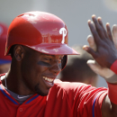 Philadelphia Phillies John Mayberry Jr. celebrates in the dugout after scoring the tying run in the eighth inning of a spring exhibition baseball game against the Minnesota Twins in Fort Myers, Fla., Sunday, March 9, 2014. The game ended in a 1-1 tie The