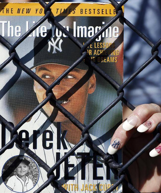 A New York Yankees fan holds Derek Jeter's autobiography, co-written with Jack Curry, hoping for Jeter's signature before a spring training baseball game against the Tampa Bay Rays in Tampa, Fla., Sunday, March 9, 2014
