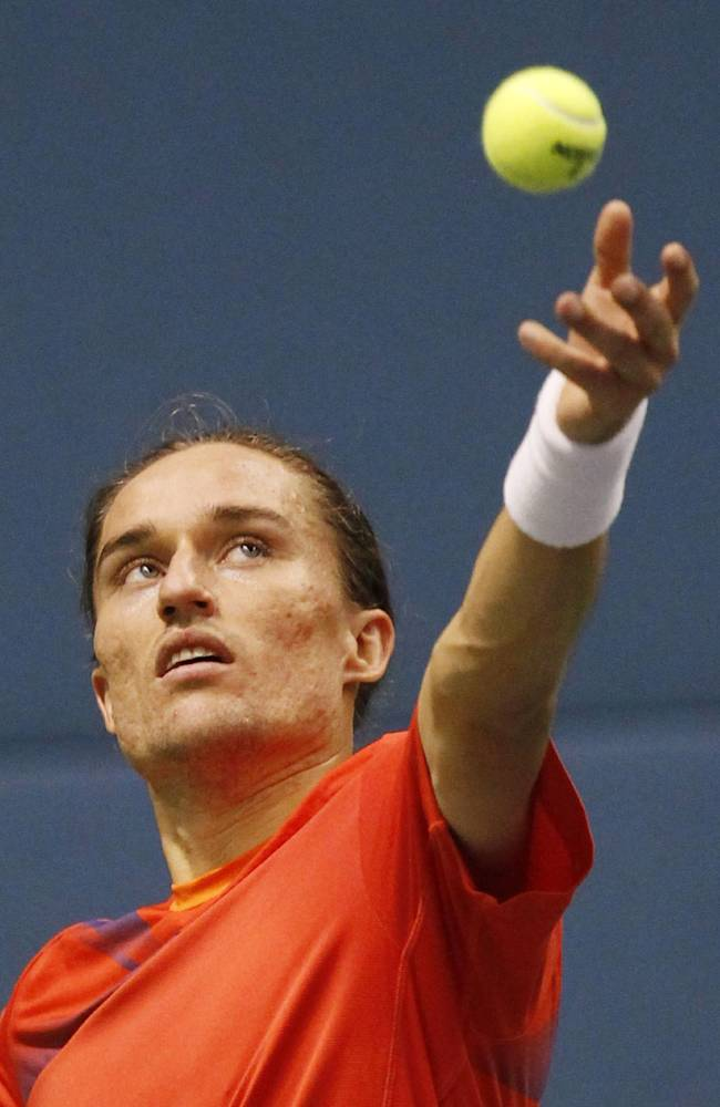 Alexandr Dolgopolov of Ukraine tosses the ball to serve against Michael Russell of the United States at the singles match of the Shanghai Masters tennis tournament at Qizhong Forest Sports City Tennis Center, in Shanghai, China, Tuesday, Oct. 8, 2013. Dolgopolov won 6-1, 6-3. (AP Photo)