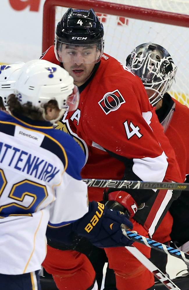 Ottawa Senators Chris Phillips (4) and goaltender Robin lehner (40) look on as St.Louis Blues Kevin Shattenkirk (22) attempts to handle a flying puck during first period NHL hockey action in Ottawa Monday, Dec. 16, 2013