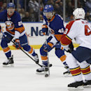 New York Islanders right wing Michael Grabner (40), of Austria, controls the puck as Islanders center Brock Nelson (29) watches with Florida Panthers defenseman Mike Weaver (43) defending in the second period of an NHL hockey game in Uniondale, N.Y., Sund