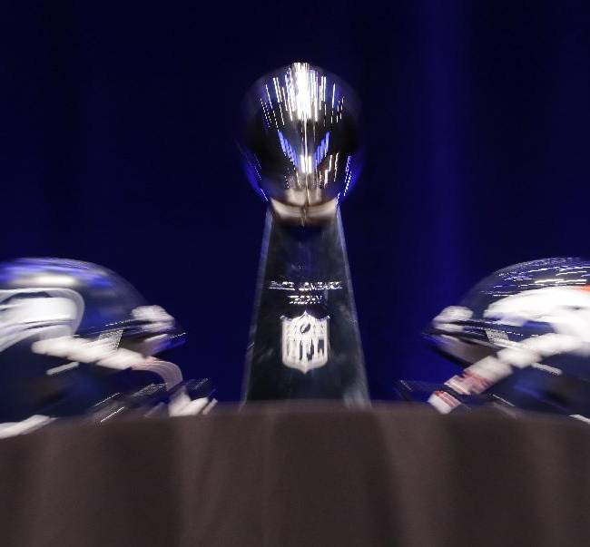 In this photograph taken while zooming out the lens during a long exposure, the Vince Lombardi Trophy is displayed between the Seattle Seahawks and the Denver Broncos helmets before a news conference Friday, Jan. 31, 2014, in New York. The Seahawks and the Broncos are scheduled to play in the NFL Super Bowl XLVIII football game on Sunday, Feb. 2, at MetLife Stadium in East Rutherford, N.J