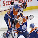 Chicago Blackhawks' Brad Richards (91) crashes the net next to Edmonton Oilers' Nikita Nikitin (86), as goalie Ben Scrivens (30) makes the save and Jordan Eberle (14) gets the rebound during the third period of an NHL hockey game Friday, Jan. 9, 2015, in