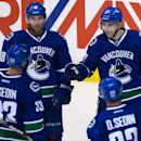 Vancouver Canucks' Radim Vrbata, of the Czech Republic; Daniel Sedin and Henrik Sedin, of Sweden; and Ryan Stanton, clockwise from top right, celebrate Vrbata's goal against the Edmonton Oilers during the second period of an NHL hockey preseason game Satu