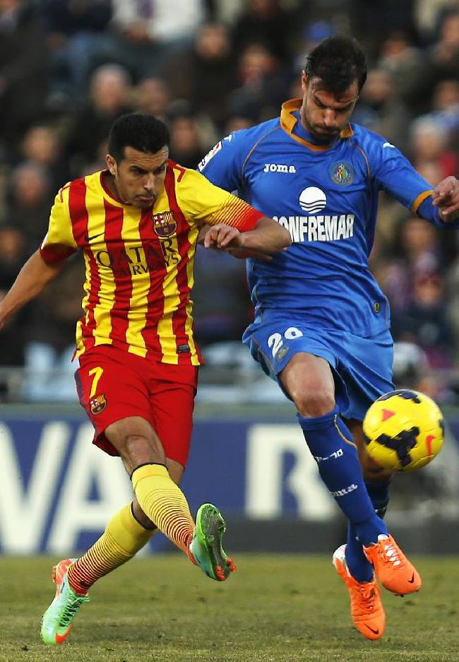 FC Barcelona's Pedro Rodriguez, left, scores his goal under pressure of Getafe's Juan Valera, right, during a Spanish La Liga soccer match between FC Barcelona and Getafe at the Coliseum Alfonso Perez stadium in Madrid, Spain, Sunday, Dec. 22, 2013