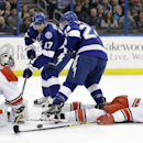 Carolina Hurricanes defenseman Tim Gleason (6) reaches back to knock the puck away from Tampa Bay Lightning center Alex Killorn (17) and right wing Ryan Callahan (24) in front of Hurricane's goalie Cam Ward (30) during the second period of an NHL hockey g