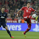 Bayern's Mario Mandzukic, right, is watched by Michael Carrick during the Champions League quarterfinal second leg soccer match between Bayern Munich and Manchester United in the Allianz Arena in Munich, Germany, Wednesday, April 9, 2014