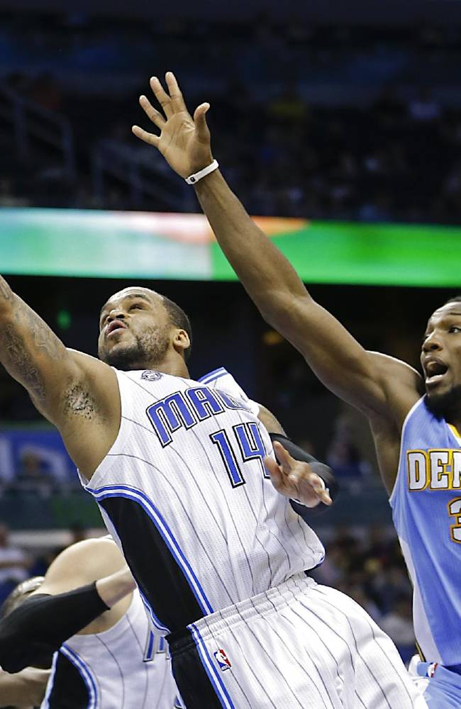 Orlando Magic's Jameer Nelson (14) gets past Denver Nuggets's Kenneth Faried (35) for a lay up during the second half of an NBA basketball game in Orlando, Fla., Wednesday, March 12, 2014. Denver won 120-112