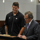 Tennessee Titans rookie NFL football player Taylor Lewan stands with his attorney John Shea, right, in Washtenaw County District Court in Ann Arbor, Mich., where he plead guilty to two misdemeanors to resolve an assualt case involving an Ohio State fan, T
