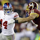 New York Giants running back Peyton Hillis (44) stiff arm's Washington Redskins outside linebacker Ryan Kerrigan (91) during the second half of an NFL football game Sunday, Dec. 1, 2013, in Landover, Md The Associated Press