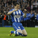 Wigan Athletic's Gary Caldwell drops to his knee after his miss in a penalty shoot-out against Arsenal during their English FA Cup semifinal soccer match at Wembley Stadium in London, Saturday, April 12, 2014