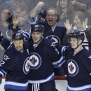 Winnipeg Jets' Olli Jokinen (12), Blake Wheeler (26) and Jacob Trouba (8) celebrate Wheeler's goal against the Phoenix Coyotes during first-period NHL hockey game action in Winnipeg, Manitoba, Thursday, Feb. 27, 2014. (AP Phoyo/The Canadian Press, John Wo