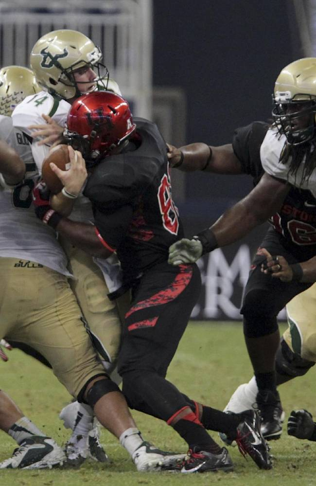 Houston defensive end Tyus Bowser, center right, sacks South Florida quarterback Mike White, center left, resulting in a fumble during the fourth quarter of an NCAA college football game Thursday, Oct. 31, 2013, in Houston. Houston won 35-23