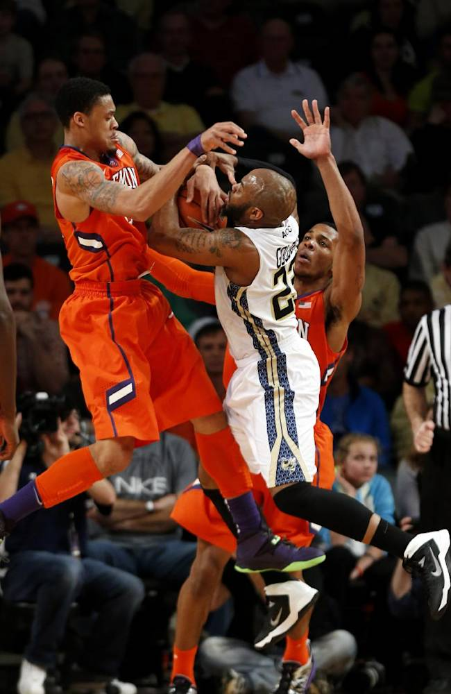 Georgia Tech guard Trae Golden (23) is wrapped up by Clemson forward K.J. McDaniels (32) as he drives to the basket in the second half of an NCAA college basketball game  Saturday, Feb. 22, 2014, in Atlanta.  Clemson won 63-55