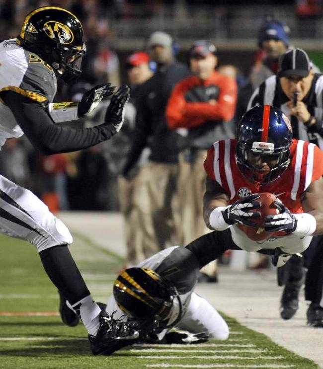 Mississippi receiver Laquon Treadwell, right, dives for a first down past Missouri defensive lineman Shane Ray, left, and Missouri defensive back Randy Ponder during the first quarter of an NCAA college football game on Saturday, Nov. 23, 2013, in Oxford, Miss