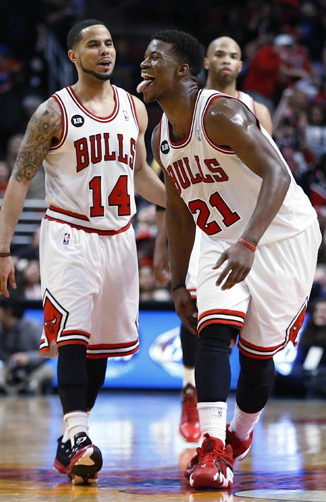 Chicago Bulls guard Jimmy Butler, right, sticks out his tongue after scoring, next to guard D.J. Augustin, left, during the second half of an NBA basketball game against the Milwaukee Bucks in Chicago, Friday, April 4, 2014. The Bulls won 102-90