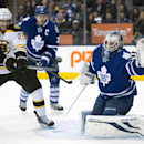 Toronto Maple Leafs goaltender James Reimer, right, prepares to make a glove save as Boston Bruins right winger Loui Eriksson (21) tries to deflect the shot while Leafs defenseman Dion Phaneuf (3) skates near during an overtime period of an NHL hockey gam