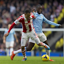 Manchester City's Yaya Toure, right, fights for the ball against Stoke's Peter Odemwingie, during their English Premier League soccer match at the Etihad Stadium, Manchester, England, Saturday Feb. 22, 2014