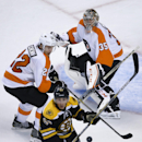 Boston Bruins left wing Brad Marchand (63) chases a loose puck as Philadelphia Flyers goalie Steve Mason (35) protects the net with defenseman Luke Schenn (22) in the first period of an NHL hockey game in Boston, Wednesday, Oct. 8, 2014 The Associated Pre