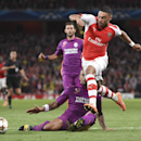 Arsenal's Alex Oxlade-Chamberlain, right, lunges past Galatasaray's Felipe Melo during the Champions League Group D soccer match between Arsenal and Galatasaray , at the Emirates Stadium in London, on Wednesday, Oct 1, 2014