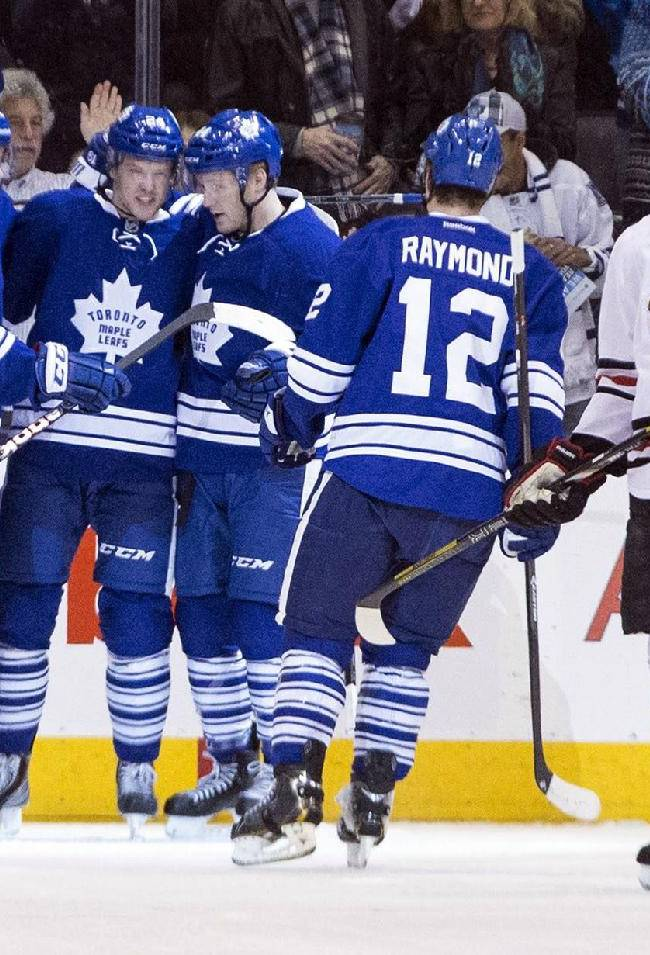 Toronto Maple Leafs' Peter Holland, center, is congratulated by teammates after scoring against the Chicago Blackhawks during the first period of an NHL hockey game in Toronto on Saturday, Dec. 14, 2013