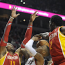 Houston Rockets' Dwight Howard (12) and Patrick Beverley (2) defend against Portland Trail Blazers' Damian Lillard (0) during the second half of an NBA basketball game in Portland, Ore.,Thursday Dec. 12, 2013. Portland beat the Rockets 111-104 The Associ