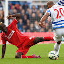 Liverpool's Mario Balotelli, left, and Queens Park Rangers' Carl Henry compete for the ball during their English Premier League soccer match at Loftus Road, London, Sunday, Oct. 19, 2014