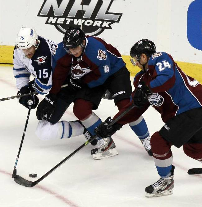 From left, Winnipeg Jets right wing Matt Halischuk battles for control of the puck with Colorado Avalanche defenseman Tyson Barrie and center Marc-Andre Cliche in the third period of the Avalanche's 3-2 victory in an NHL hockey game in Denver on Sunday, Oct. 27, 2013